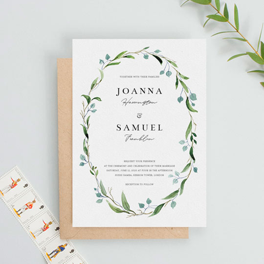 An elegant and floral wedding invitation with a beautiful green and blue watercolour wreath. The centre of the wedding invite has text made up of several contrasting fonts.