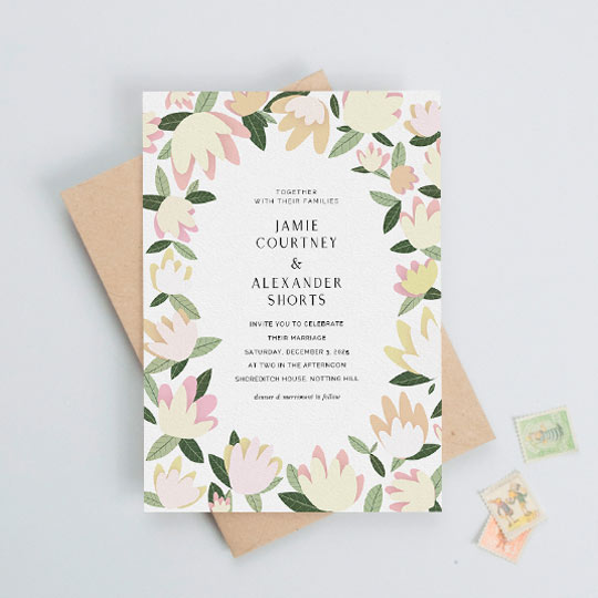 A modern floral wedding invitation design with dozens of pastel flowers and leaves forming a border around elegant wedding invitation text.