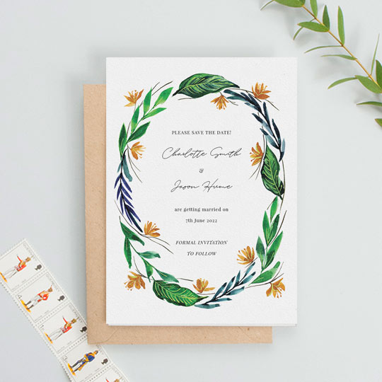 A modern, floral wedding save the date card with tropical leaved and flowers making up a painted wreath. The background of the save the date is white, and the information of an upcoming wedding is printed in the middle.