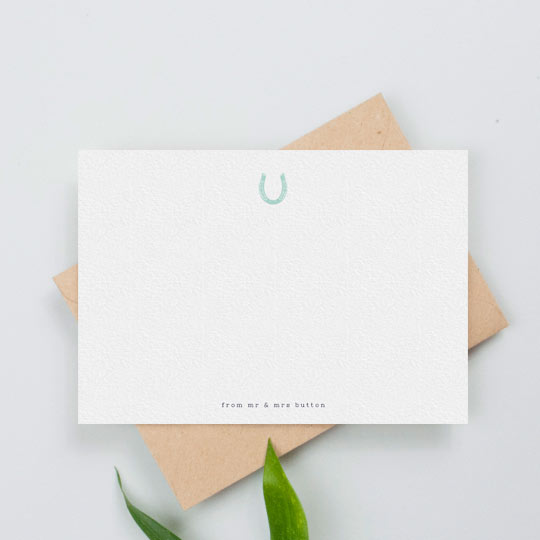 A personalised note card with a blue horseshoe printed at the top. The name of a couple if printed at the bottom.