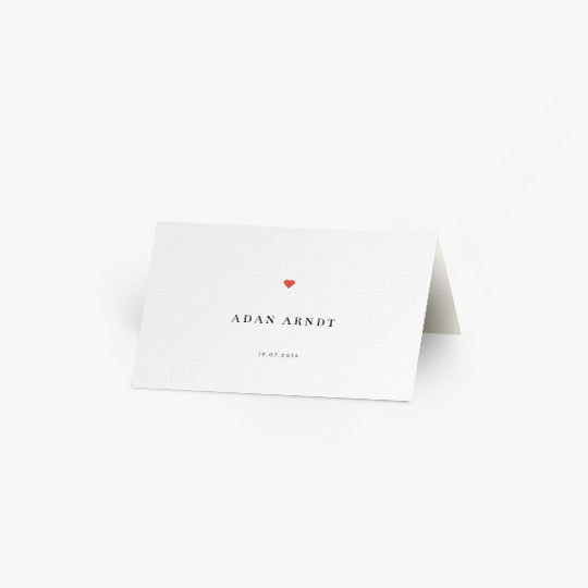 A simple, personalised place card for a wedding meal. The card has a guest's name printed on the front, with the date printed underneath. It has a small, red heart in the middle. The place card is folded and stands like a tent on a table.