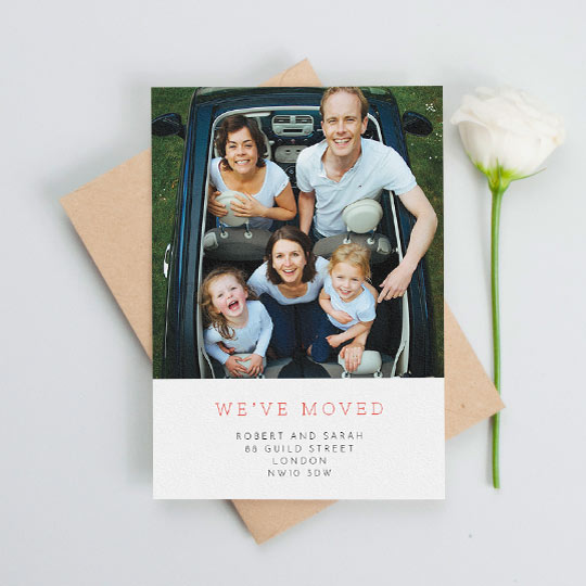 """A change of address card with a photo of a family. The card reads in red font """"We've Moved""""."""