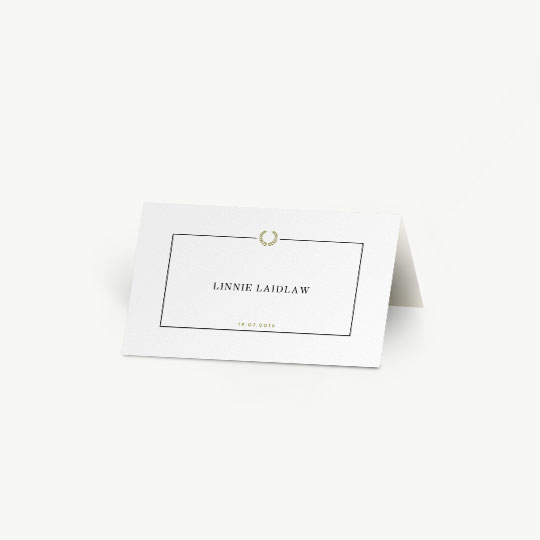 A white, tent place card, personalised with the details of a wedding guest. It has a simple black border with a gold, Greek wreath at the top-middle. The date of the wedding is printed at the bottom of the place card. It is a folded place card.