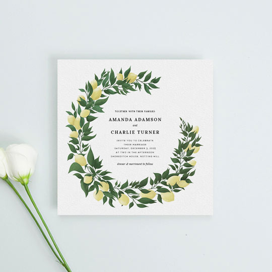 A rustic wedding invitation design made from a two-third wreath of lemons and leaves. The wreath has been hand-painted and frames some central text detailing an upcoming marriage ceremony.
