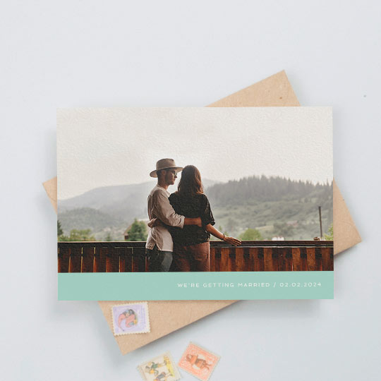 "A simple photo wedding save the date card with a full-width colour photo. It has a mint green bottom with white text reading ""we're getting married"""