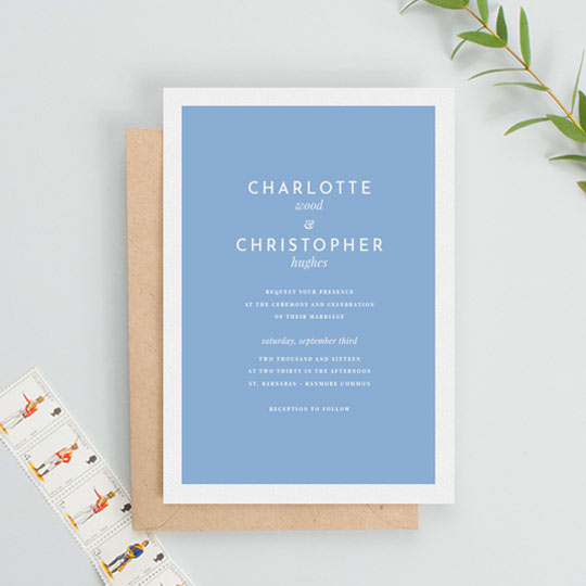 A classic and simple wedding invitation card design. The body of the wedding invitation is made of a light blue background, surrounded by a thick white border. The wedding invitation text is simplistic and classic at the same time