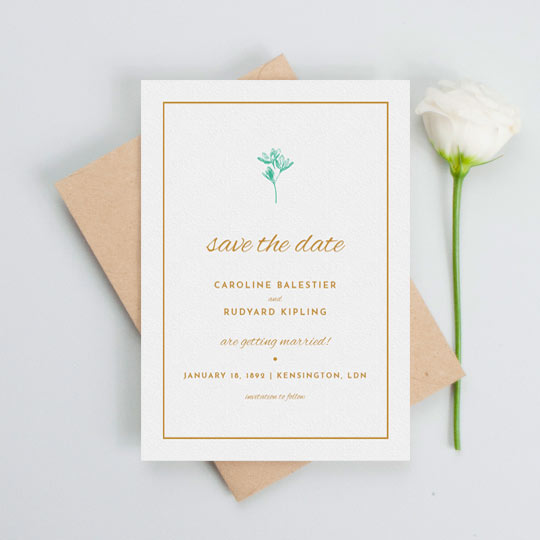 A simple wedding save the date design with a thin orange border and understated blue flower printed at the top of the card. The details of an upcoming wedding are printed in orange in a range of fonts.