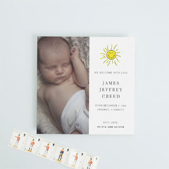 A square baby birth announcement card with a baby photo on the left-hand side. It has a hand drawn picture of the sun smiling on the right-hand side. The baby's birth details are printed underneath the sun.