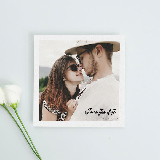 "A simple but modern wedding save the date card. It has a large, colour photo in the middle with the words ""save the date"" and the wedding date written in the bottom right"