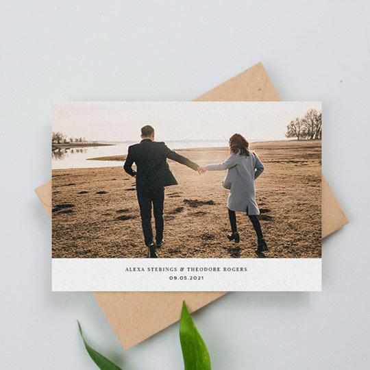 A landscape wedding invitation photo card. This is a classic design with a large colour photo on top of a white area with the names of a married couple and the date of their wedding.