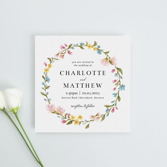 A floral wedding invitation made from a bright, summery floral wreath. The colour of the flowers on this wedding invitation are yellow, pink and blue, interspersed with green leaves.