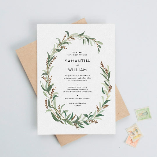 A vintage, winter-wedding invitation. The wedding invitation has a painted two-thirds wreath made up of muted green and brown leaves.