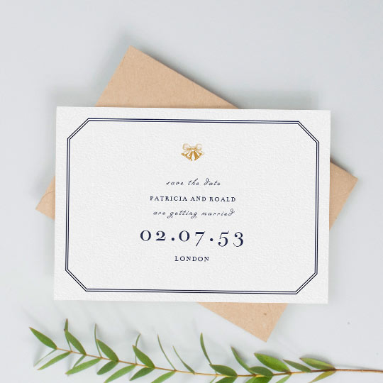 A vintage save the date wedding card. It has a classic two-lined border in navy blue, and gold wedding bells printed at the top of the card. The date of upcoming wedding is printed in a large, serif font. It is a classic save the date design.