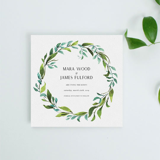 A classic, floral wedding save the date card. It is a square wedding save the date with a green and blue wreath around the outside. The floral wreath on the save the date card is hand painted in watercolour.