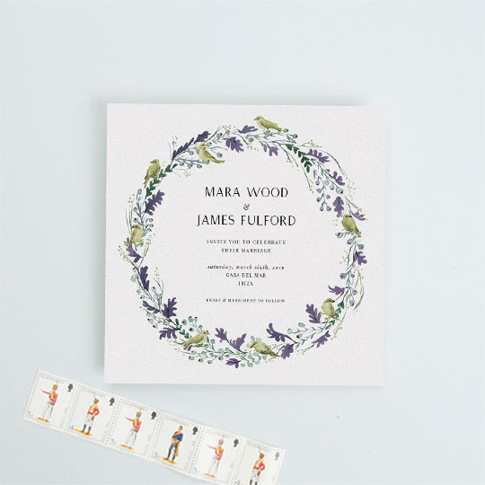 A square wedding invitation design made up of a yellow and purple wreath of oak leaves and songbirds.