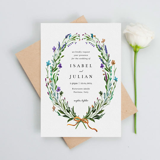 A rustic floral wedding invitation made of painted wildflowers. The wreath is very rustic, and frames centralised black text.