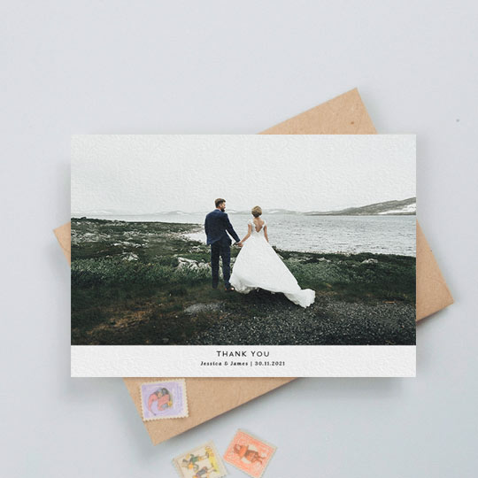 A landscape photo wedding thank you card design with a large colour photo of a married couple. Underneath is a think white section with a personalised message of thanks from the bride and groom