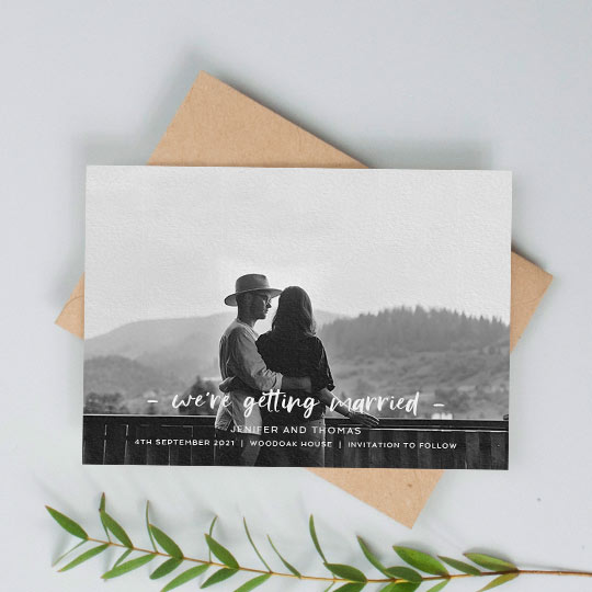 "A modern, photo wedding save the date card with ""we're getting married"" written across the bottom of the card. The save the date has a full-page, black and white photo."