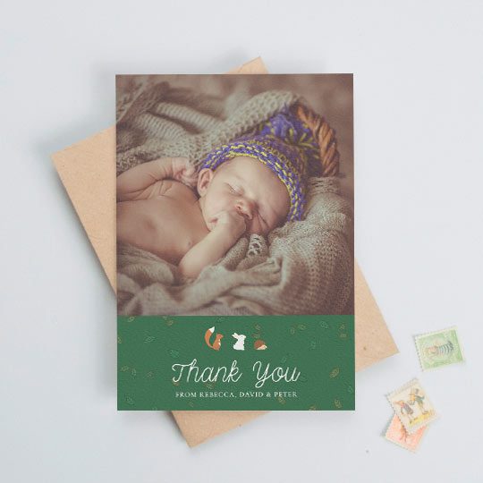 "A baby thank you card with a baby photo at the top with a green, leaf-patterned section below. There are woodland animals above the words ""thank you""."
