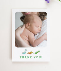 A baby thank you card with dinosaurs. The thank you cards has a large portrait photo of a baby boy.