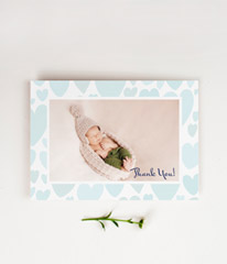 A photo baby boy thank you card. The photo of the baby is surrounded by baby blue hearts.
