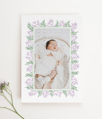 A portrait orientated baby thank you card with a baby photo in the middle. It has a modern floral border.