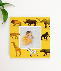 A yellow square baby thank you card with a photo of a baby boy in the middle. The border is printed with hand drawn safari animals.