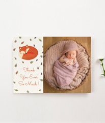 A landscape baby thank you card printed with a large photo of a baby girl. To the left of the card is a message of thanks under a hand drawn baby fox.