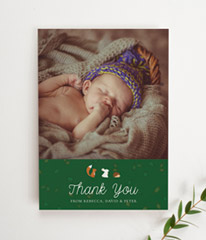 A personalised baby thank you card with a photo of a baby boy. The bottom third of the card is green with woodland animals printed.