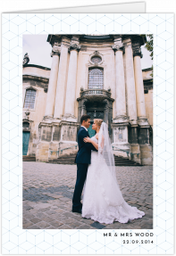 A portrait wedding thank you card with a large photo on the front cover. It is framed by a light blue geometric border.