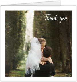 "A square photo wedding thank you card with a single, large photo of a married couple in the middle. ""Thank you"" sits in the corner."