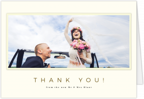 A landscape wedding thank you card with a torn photo frame. 'Thank you' is written in gold underneath the photo.