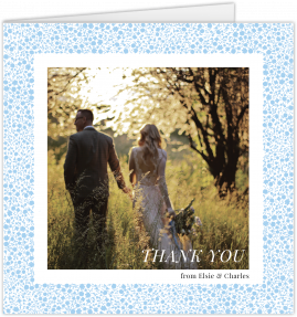 "A square wedding thank you card with a light blue flower pattern making a border around a centralised photo. ""Thank you"" is written over the photo."