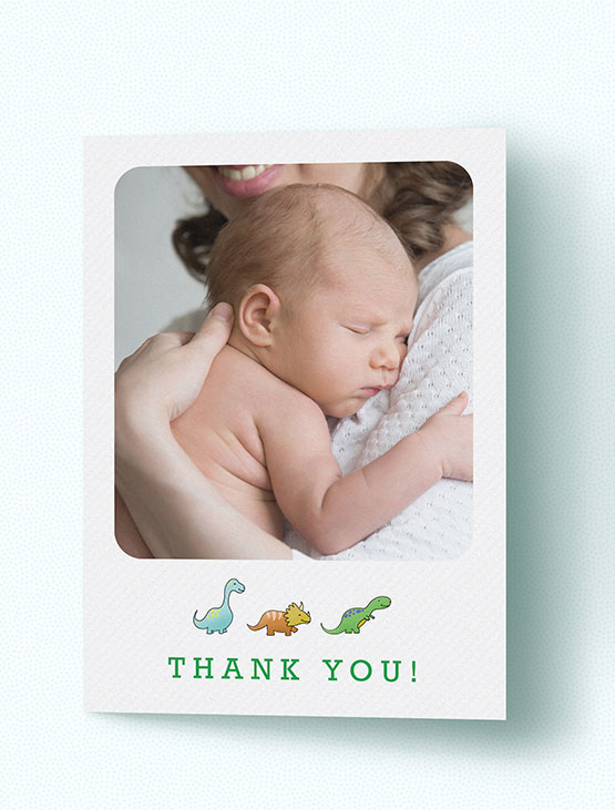 A folded baby thank you card with photo and dinosaurs
